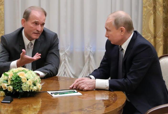 FILE - In this Thursday, July 18, 2019 file photo, Russian President Vladimir Putin's close associates, Ukrainian tycoon Viktor Medvedchuk, left, speaks to Russian President Vladimir Putin during their meeting in St. Petersburg, Russia. Medvedchuk, who heads the Opposition Platform for Life party and has close ties with Putin, was placed under house arrest on Thursday, May 13, 2021 by a Ukrainian court on treason charges that he denied. (Mikhail Klimentyev, Sputnik, Kremlin Pool Photo via AP, File)