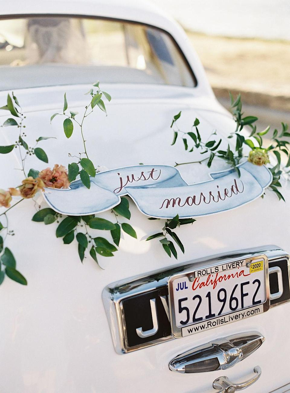 "<p>Post portraits, the pair hopped into a vintage Bentley adorned with a ""Just Married"" sign and greenery and made their way to the party venue.</p>"