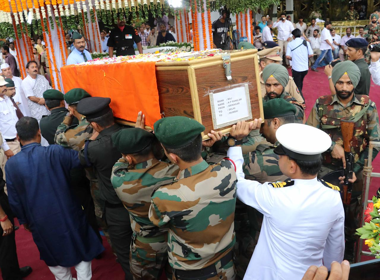 <p>People carry the coffin containing the body of Indian Army Major Kaustubh Rane, who was killed in a gun battle Tuesday in Kashmir, during his funeral procession outside his home in Mumbai, India, Thursday, Aug 9, 2018. (Yahoo India/Stringer) </p>