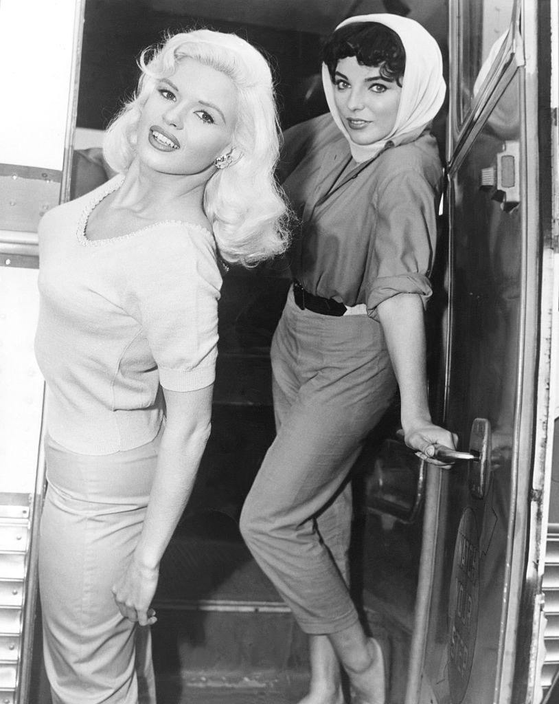 <p>Jayne Mansfield and Joan Collins pop out of a trailer on the set of their film, <em>The Wayward Bus,</em> in 1957. The film was an adaption of John Steinbeck's novel and was one of Mansfield's first major roles in film. </p>