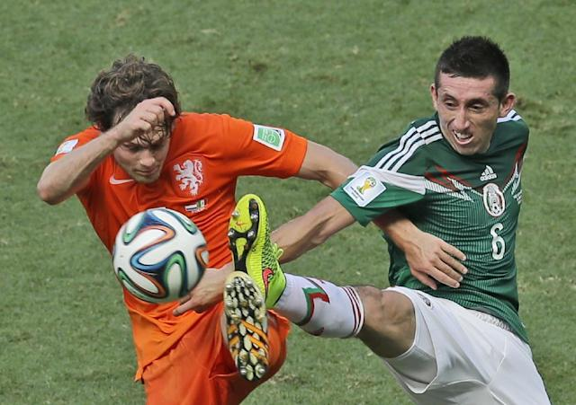 Netherlands' Daley Blind, left, and Mexico's Hector Herrera challenge for the ball during the World Cup round of 16 soccer match between the Netherlands and Mexico at the Arena Castelao in Fortaleza, Brazil, Sunday, June 29, 2014. (AP Photo/Themba Hadebe)