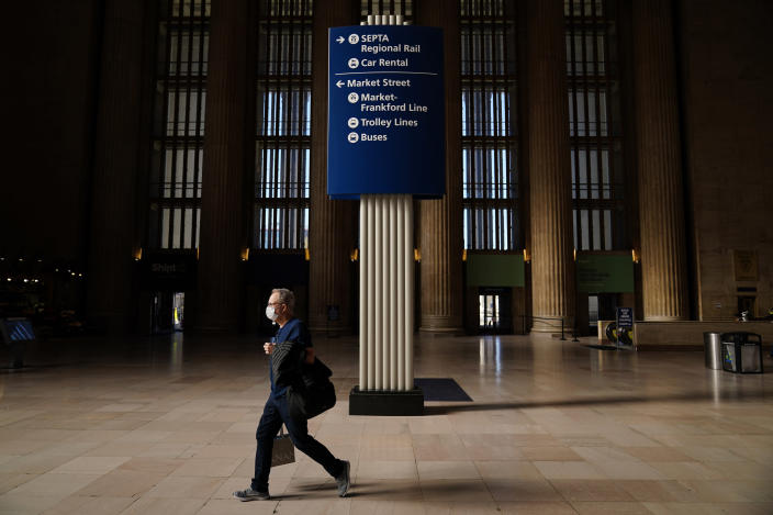 A traveler walks through the 30th Street Station ahead of the Thanksgiving holiday, Friday, Nov. 20, 2020, in Philadelphia. With the coronavirus surging out of control, the nation's top public health agency pleaded with Americans not to travel for Thanksgiving and not to spend the holiday with people from outside their household. (AP Photo/Matt Slocum)
