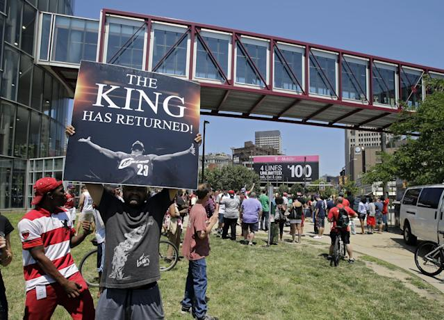 Graphic designer Alvin Smith holds up a poster across the street from the Quicken Loans Arena in Cleveland, Friday, July 11, 2014, heralding the return of NBA basketball star LeBron James. James, who left the Cleveland Cavaliers four years ago to join the Miami Heat, announced earlier he would return to the Cavaliers. (AP Photo/Mark Duncan)