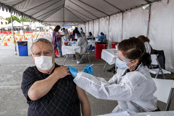 Nurse Susan Eyman administers the Moderna vaccine to Robert Nelson in the parking lot of the Riverside Convention Center