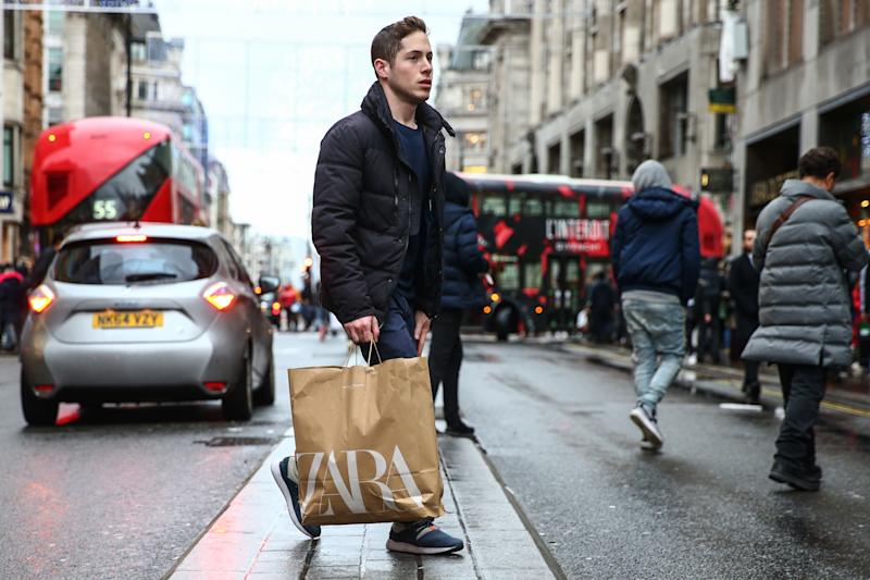 LONDON, ENGLAND - DECEMBER 26: A shopper crosses Oxford Street during the annual Boxing Day Sales on December 26, 2019 in London, England. (Photo by Hollie Adams/Getty Images)