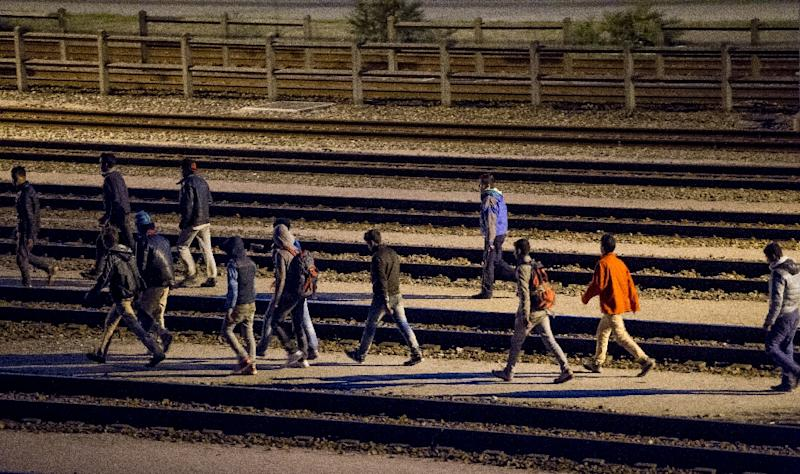 Migrants walk along railway tracks at the Eurotunnel terminal on July 28, 2015 in Calais-Frethun (AFP Photo/Philippe Huguen)