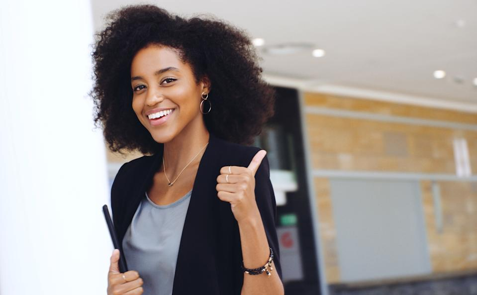Portrait of a confident young businesswoman showing a thumbs up gesture in a modern office