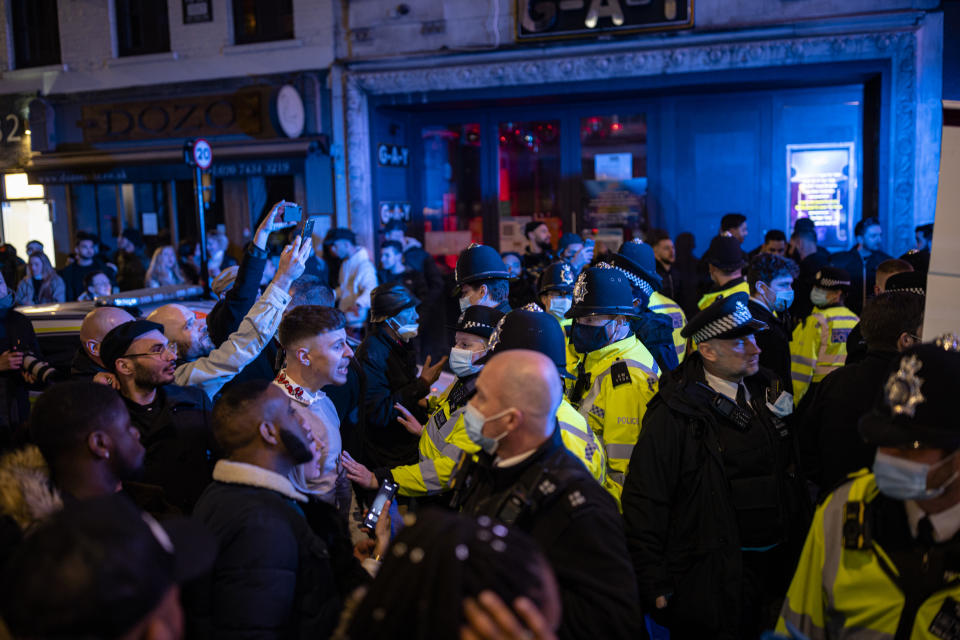 LONDON, ENGLAND - APRIL 16: Police officers attempt to keep the crowd away from a police van after a man was arrester on Old Compton Street in Soho on April 16, 2021 in London, England. Pubs and Restaurants are expecting good business tonight being the first Friday night after Coronavirus lockdown rules were relaxed to allow outside dining and drinking. (Photo by Rob Pinney/Getty Images)