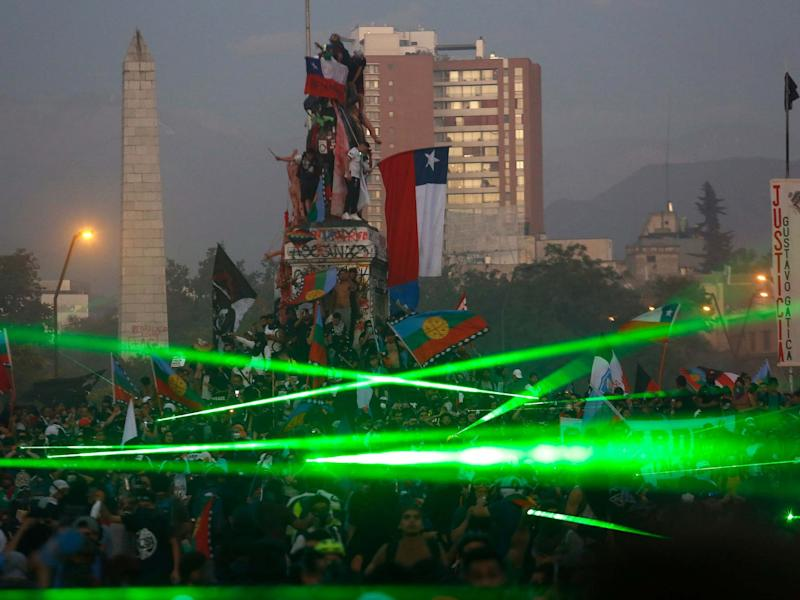 Demonstrators take on riot police using green laser lights in Santiago, Chile, on 15 November: Getty Images