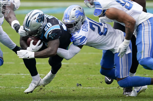 Carolina Panthers running back Mike Davis is tackled by Detroit Lions cornerback Amani Oruwariye during the second half of an NFL football game Sunday, Nov. 22, 2020, in Charlotte, N.C. (AP Photo/Gerry Broome)
