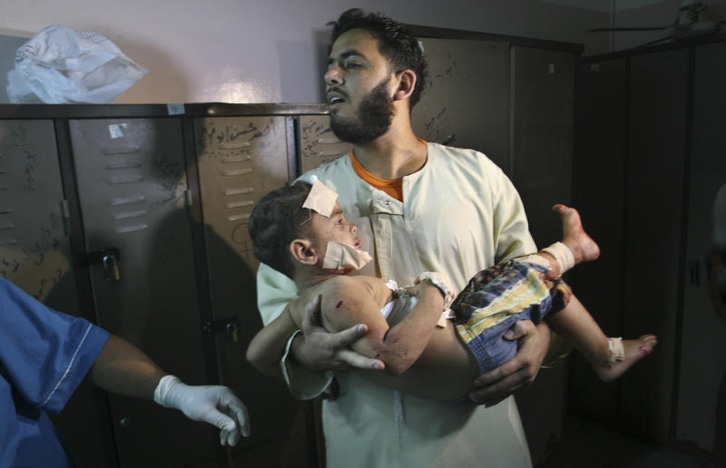 """A Palestinian man carries a wounded boy in Al Najar Hospital following an Israeli air strike in Rafah, southern Gaza Strip, Sunday, Oct. 7, 2012. Israel's military says it has fired on two Gaza members of an al-Qaida-inspired group identified as having been involved in rocket attacks and an infiltration from Egypt. Palestinians say one man was killed. The military said they were involved in """"extensive terrorist activity,"""" including an attack in June where two gunmen crossed into Israel from the Sinai desert and killed a civilian.Israel did not say whether it hit the two. Ashraf al-Kidra, a Palestinian health official in Gaza said one man was killed and another injured Sunday when their motorcycle was hit by aircraft in the south of the Hamas-controlled territory. Israel and Hamas have mostly kept an unwritten truce since a short war over three years ago. Attacks have persisted but at a much lower rate. (AP Photo/Eyad Baba)"""