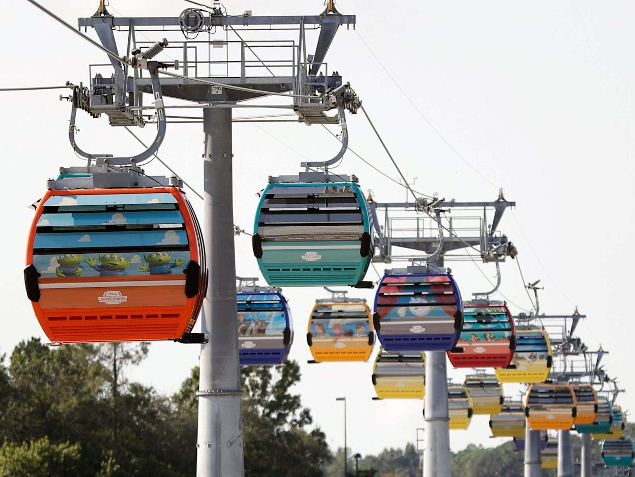 Firefighters have responded to help Walt Disney World holiday-goers who have been stuck aboard the Florida resort's newly launched aerial cable car system: AP Photo/John Raoux