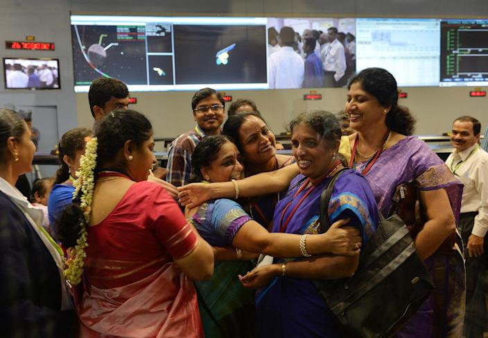 Indian staff from the Indian Space Research Organisation (ISRO) celebrate after the Mars Orbiter Spacecraft (MoM) successfully entered the Mars orbit at the ISRO Telemetry, Tracking and Command Network (ISTRAC) in Bangalore on September 24, 2014. India became the first nation to reach Mars on its maiden attempt September 24 when its low-cost Mangalyaan spacecraft successfully entered orbit around the Red Planet after a 10-month journey. The photo in itself was a revelation – not just about the female presence in India's efforts to understand the larger universe, but also about how relatable they are. The saree-clad women with gajras could just be the women you see in your daily lives – just going on about their normal routines, which in their case included sending a spacecraft as part of India's first inter-planetary mission. (Photo: Manjunath Kiran/AFP via Getty Images)
