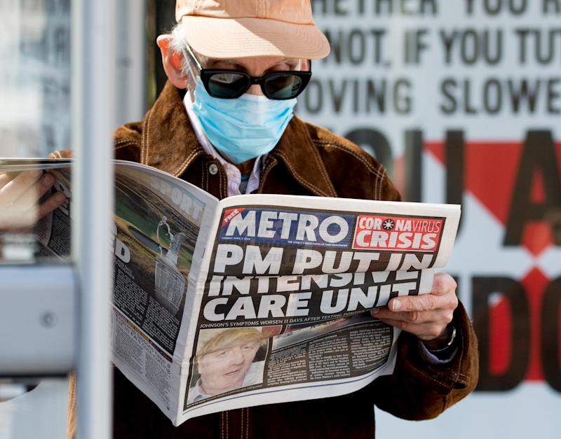 LONDON, ENGLAND - APRIL 07: A man wearing a protective mask reads a story in the Metro newspaper about Boris Johnson while standing outside St Thomas' Hospital in Westminster, where the British Prime Minister has been transferred to the ICU after showing persistent symptoms of coronavirus (COVID-19) for 10 days, on April 7, 2020 in London, United Kingdom. At 7pm last night an announcement was made that the Prime Minister had been moved to intensive care at St Thomas' Hospital after his symptoms worsened. (Photo by Ollie Millington/Getty Images)