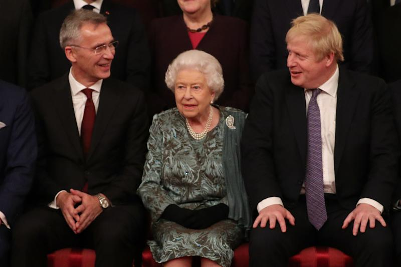 NATO Secretary General Jens Stoltenberg, Britain's Queen Elizabeth II and Britain's Prime Minister Boris Johnson sit together at Buckingham Palace in central London on December 3, 2019, as leaders of Nato alliance countries, and its secretary general, join Queen Elizabeth II and the Prince of Wales for a group picture to mark 70 years of the alliance ahead of the NATO alliance summit. - NATO leaders gather Tuesday for a summit to mark the alliance's 70th anniversary but with leaders feuding and name-calling over money and strategy, the mood is far from festive. (Photo by Yui Mok / POOL / AFP) (Photo by YUI MOK/POOL/AFP via Getty Images)
