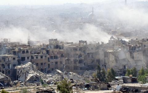 Smoke billowing from the Palestinian camp of Yarmouk during regime strikes targeting the Islamic State group in the camp - Credit: Stringer/AFP