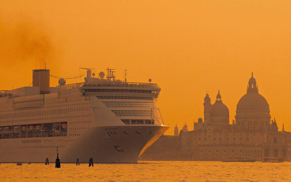 A cruise ship creeps past Venice at sunset - istock
