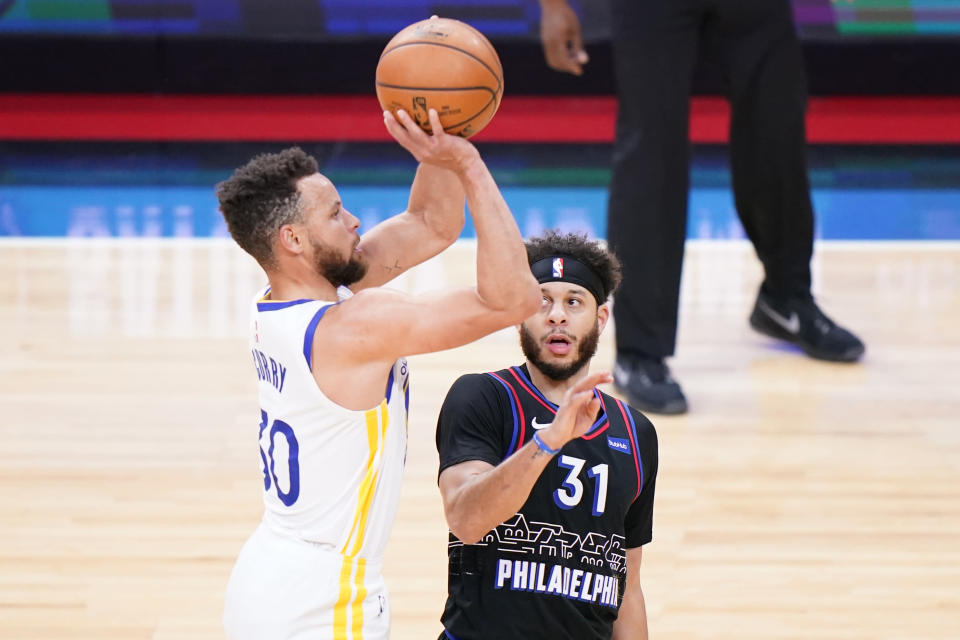 Golden State Warriors' Stephen Curry, left, goes up for a shot past Philadelphia 76ers' Seth Curry during the first half of an NBA basketball game, Monday, April 19, 2021, in Philadelphia. (AP Photo/Matt Slocum)