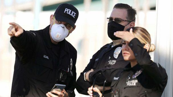 PHOTO: LAPD officers, some wearing masks, keep watch after the USNS Mercy Navy hospital ship arrived in the Port of Los Angeles to assist with the coronavirus pandemic on March 27, 2020 in San Pedro, California. (Mario Tama/Getty Images)