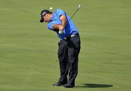 Jun 28, 2014; Bethesda, MD, USA; Patrick Reed hits his approach shot on the 14th hole during the third round of the Quicken Loans National golf tournament at Congressional Country Club - Blue Course. Mandatory Credit: Tommy Gilligan-USA TODAY Sports - RTR3W8QO