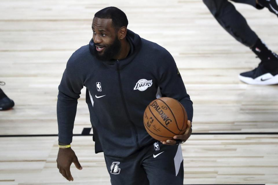LeBron James in a black warm-up jacket holds a basketball on a court.