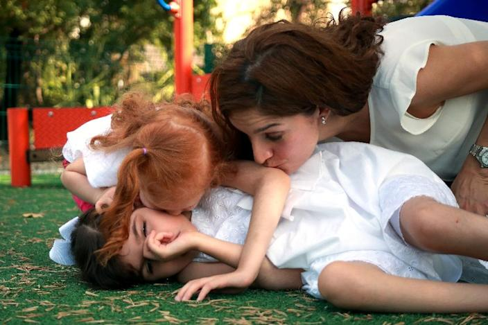 Mayela Benavides play with her daughters Graciela (L) and Valentina in a park in the Guadalupe municipality near Monterrey (AFP Photo/Carlos Ramirez)