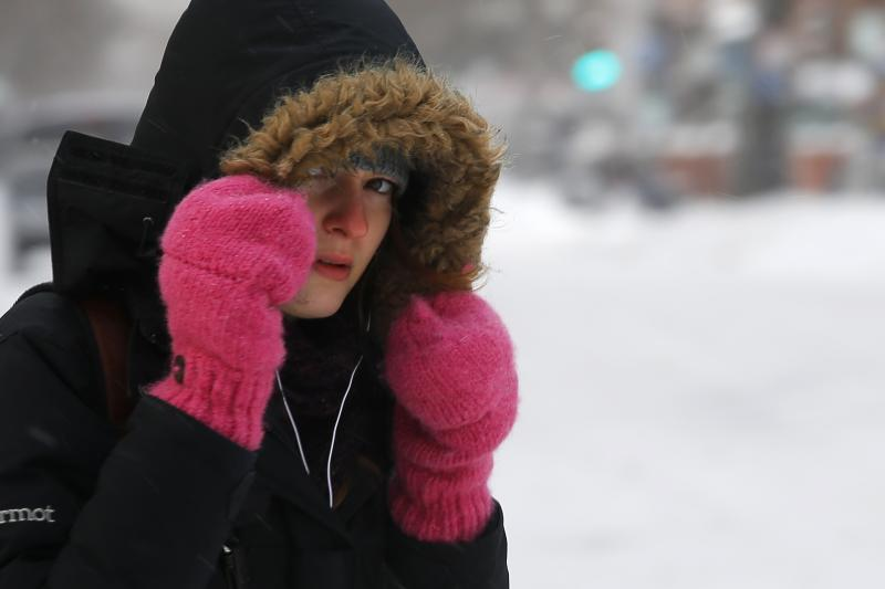 A woman crosses the street following a winter nor'easter snowstorm in Boston