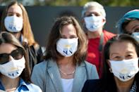 """Baltimore Sun reporter Liz Bowie (C) wears a """"Save Our Sun"""" facemask at a gathering with other journalists gathering March 11 outside the headquarters of the newspaper which has a tentative deal to be acquired by a nonprofit organization"""