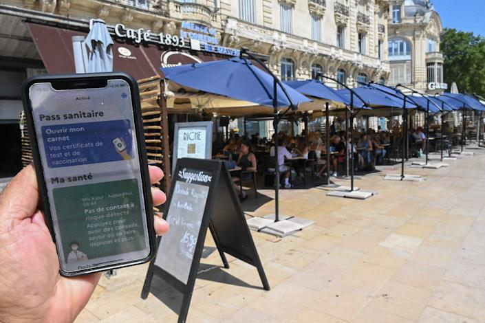 A man shows a digital sanitary pass document on his smartphone in front of a restaurant in southern France on Wednesday. France began enforcing a COVID-19 pass in cafes, restaurants and trains.