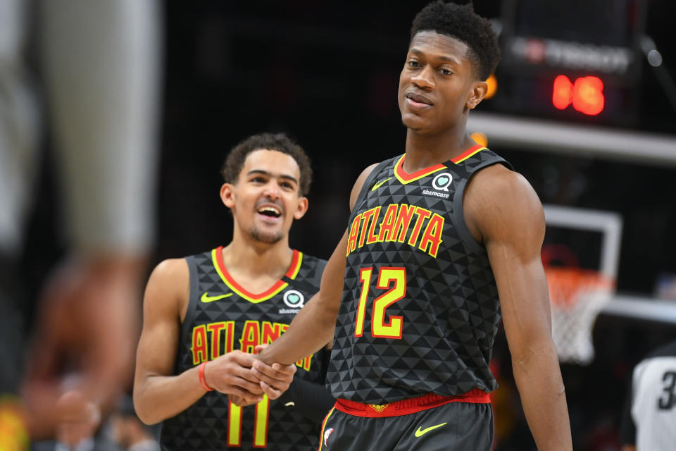 Atlanta Hawks forward De'Andre Hunter (12) is congratulated by guard Trae Young (11) as they come to the bench after Hunter hit three free throws to go ahead against the Charlotte Hornets during the second overtime in an NBA basketball game Monday, March 9, 2020, in Atlanta. (AP Photo/John Amis)