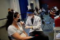 FILE PHOTO: A woman receives a dose of the Johnson & Johnson coronavirus disease (COVID-19) vaccine during a visit of U.S. Vice President Kamala Harris to a vaccination center in Chinatown, in Chicago