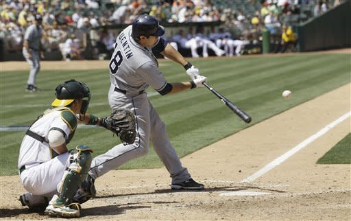 San Diego Padres' Carlos Quentin (18) hits a two-run home run off Oakland Athletics pitcher Tyson Ross during the sixth inning of a baseball game in Oakland, Calif., Saturday, June 16, 2012. At left is Athletics catcher Kurt Suzuki. (AP Photo/Jeff Chiu)