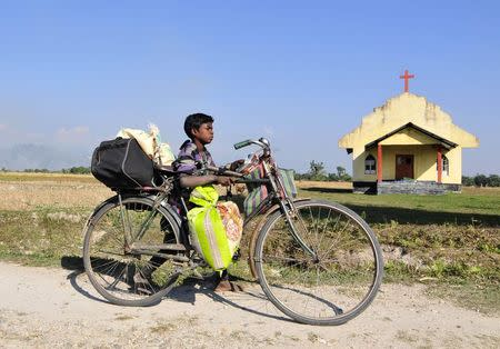 A boy transports his belongings on a bicycle as he moves to a safer place after ethnic clashes in Tenganala village, in Sonitpur district in the northeastern Indian state of Assam on December 24, 2014.  REUTERS/Stringer