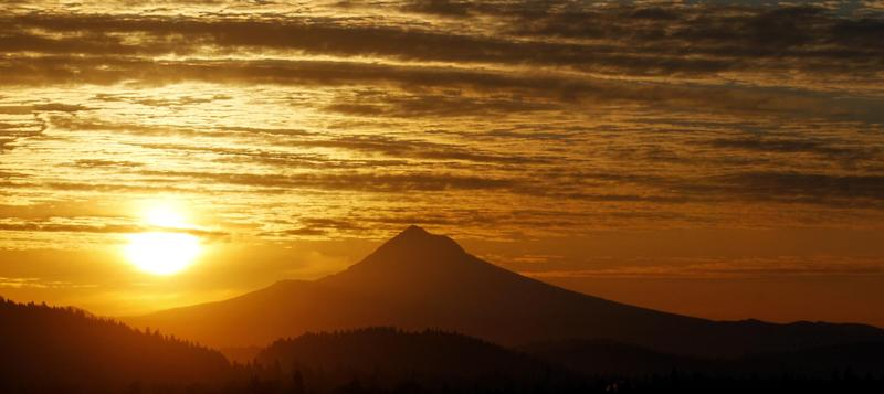 The sun rises over Mount Hood in Portland, Ore. on Thursday, March 8, 2012. The largest solar storm in five years has engulfed Earth, but scientists say the planet has lucked out so far. The storm arrived more peacefully Thursday morning than it could have. Scientists say that could change as the storm spends the day shaking the planet's magnetic field. It could disrupt technology but also spread colorful Northern Lights. (AP Photo/Rick Bowmer)