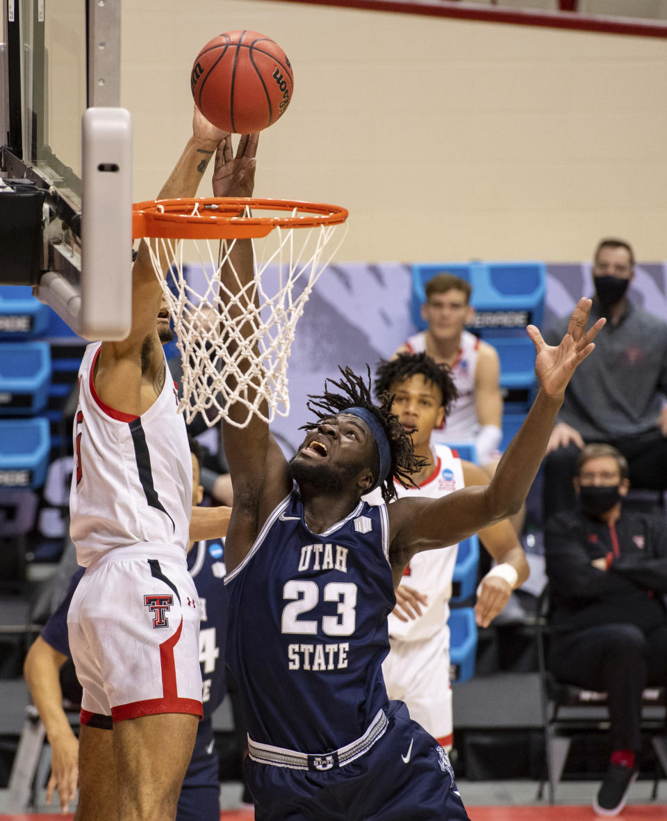 Utah State center Neemias Queta (23) blocks a shot by Texas Tech guard Micah Peavy (5) during the second half of a first round game in the NCAA men's college basketball tournament, Friday, March 19, 2021, at Assembly Hall in Bloomington, Ind. (AP Photo/Doug McSchooler)