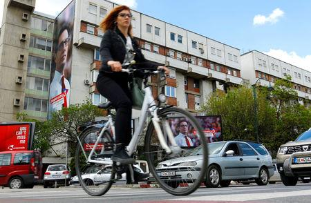 A woman passes election campaign posters of the ruling party candidate Stevo Pendarovski for presidential election on April 21 in Skopje, North Macedonia April 19, 2019. REUTERS/Ognen Teofilovski