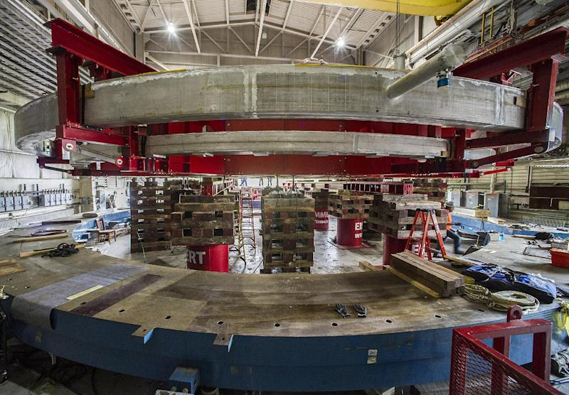 A June 11, 2013, photo provided by Brookhaven National Laboratory shows a red stabilizing apparatus carrying a 50-foot-wide electromagnet storage ring, at Brookhaven National Laboratory in Upton, N.Y., on eastern Long Island. The ring, which will capture subatomic particles that live only 2.2 millionths of a second, will be transported in one piece, and moved flat, to its new home at the U.S. Department of Energy's Fermi National Accelerator Laboratory in Batavia, Ill. (AP Photo/Brookhaven National Laboratory)