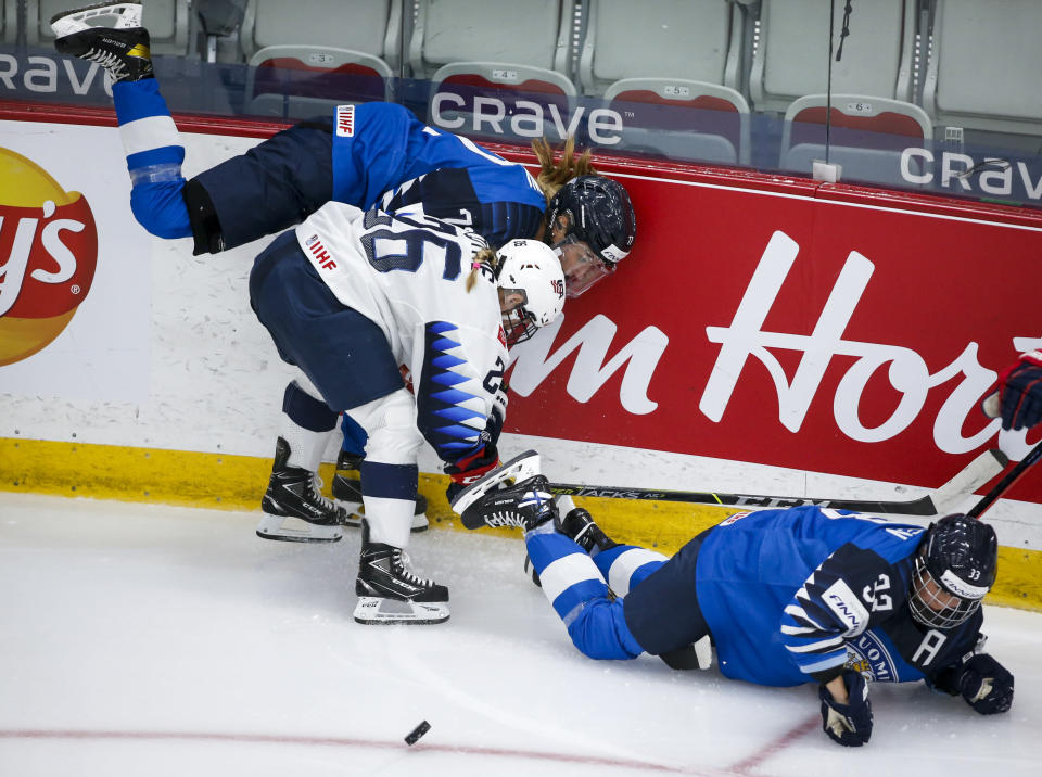 Finland's Michelle Karvinen, right, and Susanna Tapani, top left, are checked by Kendall Coyne Schofield, of the United States, during the second period of an IIHF women's hockey championships semifinal in Calgary, Alberta, Monday, Aug. 30, 2021. (Jeff McIntosh/The Canadian Press via AP)