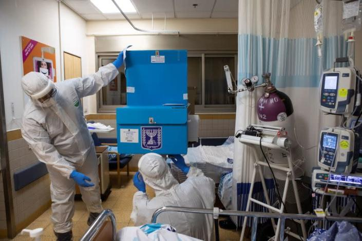 Hospital employees adjust a mobile voting booth and box inside in a ward for the treatment of the coronavirus disease (COVID-19), to enable the ward's patients to vote in Israel's general election, at Sheba Medical Center in Ramat Gan
