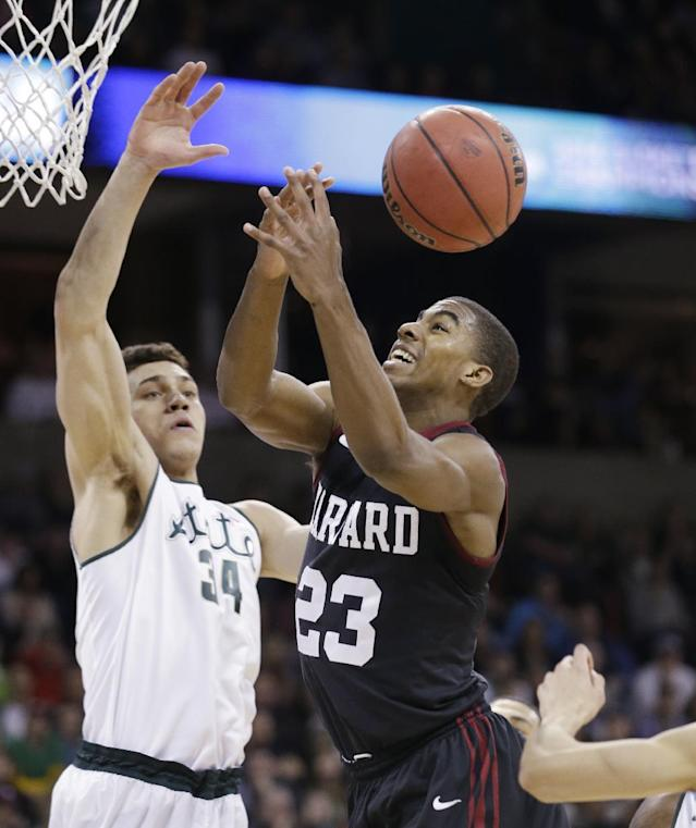 Harvard's Wesley Saunders (23) and Michigan State's Gavin Schilling eye a loose ball in the first half during the third round of the NCAA men's college basketball tournament in Spokane, Wash., Saturday, March 22, 2014. (AP Photo/Elaine Thompson)