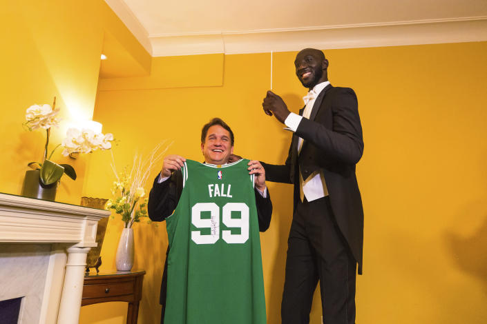 In this Monday, Dec. 23, 2019, photo provided by Boston Pops, Boston Celtics player Tacko Fall, right, poses for a photo with Boston Pops Orchestra conductor Keith Lockhart in Boston. Fall made his debut as a guest conductor during the renowned Boston Pops orchestra's holiday concert on Monday. (Robert Torres/Boston Pops via AP)
