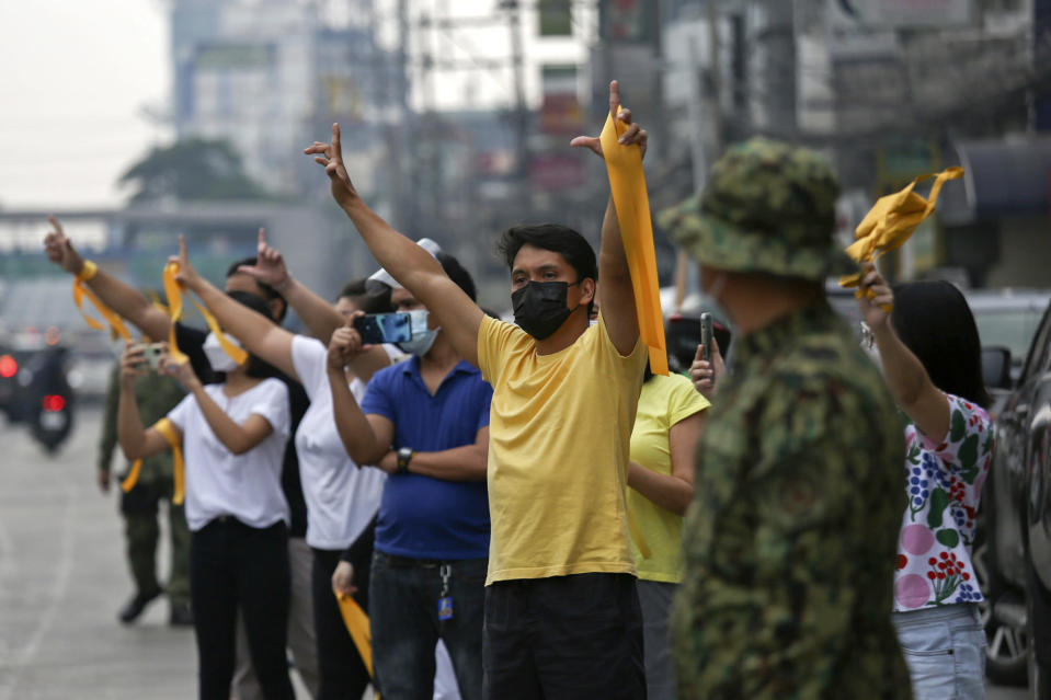 """Supporters of former Philippine President Benigno Aquino III flash the """"L"""" sign meaning """"Fight!"""" during a motorcade before his burial in Quezon City, Philippines on Saturday, June 26, 2021. Aquino was buried in austere state rites during the pandemic Saturday with many remembering him for standing up to China over territorial disputes, striking a peace deal with Muslim guerrillas and defending democracy in a Southeast Asian nation where his parents helped topple a dictator. He was 61. (AP Photo/Basilio Sepe)"""