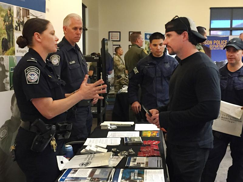 U.S. Customs and Border Protection recruiter Kelly Ursu talks with Michael Hamilton, a 28-year-old criminal justice degree graduate of Northern Arizona University who is considering applying for a job with the agency at a job fair at Pima Community College in Tucson, Ariz., Monday, Nov. 9, 2015. U.S. Customs and Border Protection is pushing to close a staffing shortage at Arizona ports of entry that business leaders say negatively impacts trade and commerce. (AP Photo/Astrid Galvan)