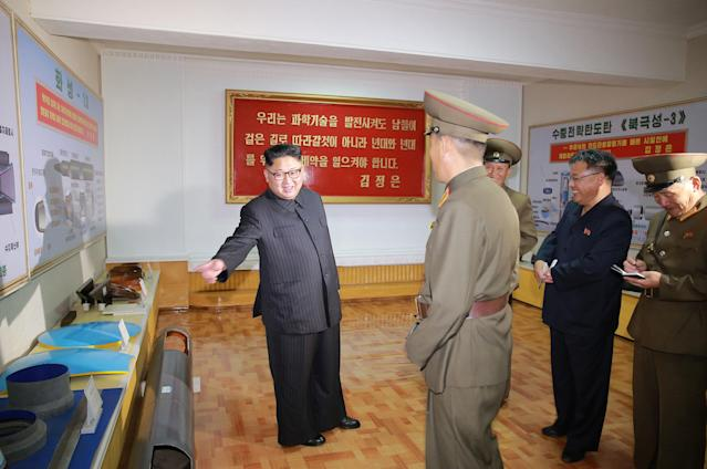 <em>Kim Jong-un was pictured at a factory inspection with wall charts of the weapons in the background (Reuters)</em>