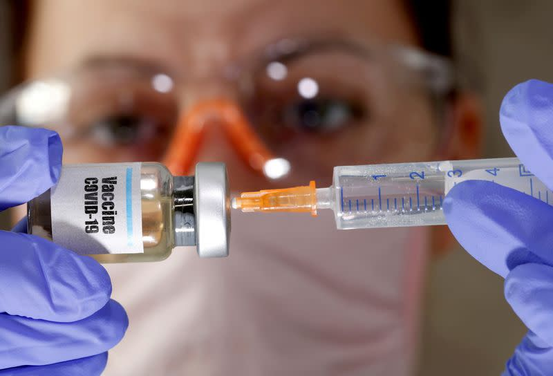 "FILE PHOTO: A woman holds a small bottle labeled with a ""Vaccine COVID-19"" sticker and a medical syringe in this illustration"