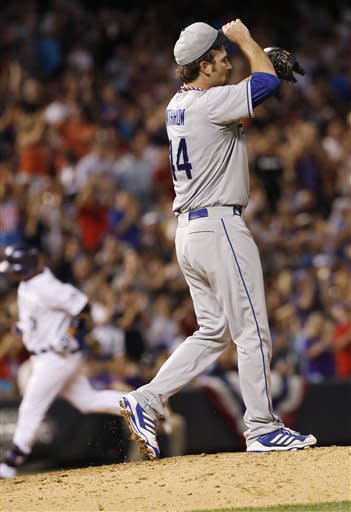 Los Angeles Dodgers relief pitcher Chris Withrow, front, reacts after giving up a solo home run to Colorado Rockies' Michael Cuddyer, back, in the seventh inning of the Rockies' 9-5 victory in a baseball game in Denver, Thursday, July 4, 2013. (AP Photo/David Zalubowski)