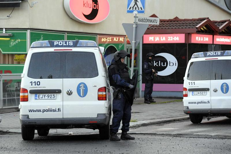Police officers guard the area in Hyvinkaa, Finland, where a gunman has killed one person and wounded eight others in what appeared to be a random shooting, police said Saturday May 26, 2012. (AP Photo/Lehtikuva/Sari Gustafsson) FINLAND OUT