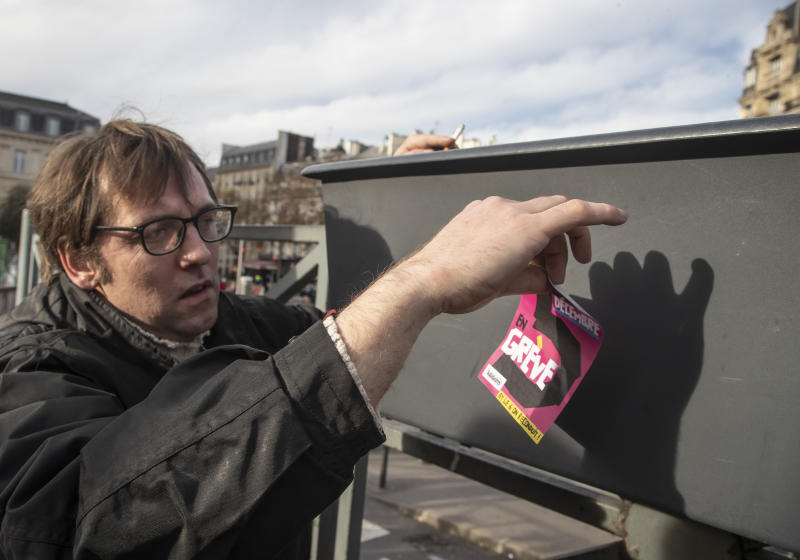 In this photo taken Saturday Nov. 30, 2019, Gilles Pierre, a metro driver for the Paris public transport company RATP, puts a sticker promoting the Dec. 5, 2019, strike, outside the Gare de Lyon train station in Paris. France is getting ready for massive, nationwide transport strikes Thursday, disrupting trains, buses and airlines, protesting against government plans to overhaul the state pension system. (AP Photo/Michel Euler)