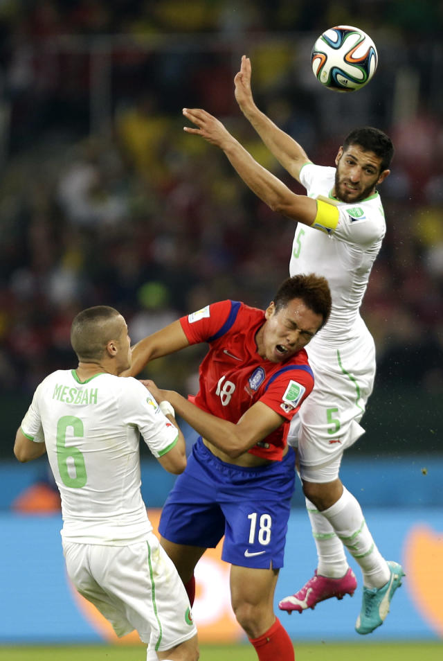 South Korea's Kim Shin-wook, centre, is challenged by Algeria's Rafik Halliche, rear, and Algeria's Djamel Mesbah during the group H World Cup soccer match between South Korea and Algeria at the Estadio Beira-Rio in Porto Alegre, Brazil, Sunday, June 22, 2014. (AP Photo/Fernando Vergara)