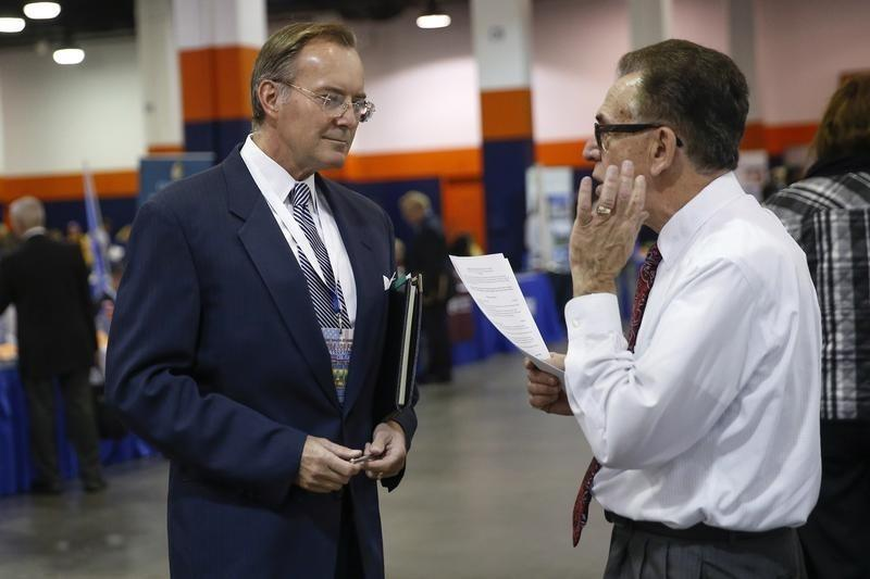 A man speaks with a job recruiter at the Nassau County Mega Job Fair at Nassau Veterans Memorial Coliseum in Uniondale, New York
